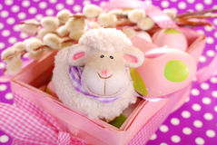 Easter basket with eggs and sheep figurine. Pink easter basket with eggs and funny sheep figurine on purple dotted background royalty free stock images