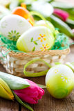 Easter basket,eggs and tulips on wooden board Royalty Free Stock Photos