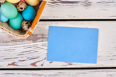 Easter basket with empty card. Paper on white wooden background. Send Easter letter to friend Stock Photos