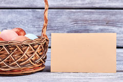 Easter basket and empty card. Paper on wooden surface Stock Photo
