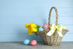 Easter basket filled with colorful eggs and flowers on a background stock photos