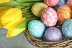 Easter basket filled with colorful eggs and flowers on a wooden background stock images