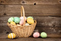 Easter basket filled eggs over rustic wood Stock Photography
