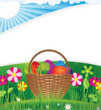 Easter basket on the morning lawn. Basket with Easter eggs on the background of open flowers Royalty Free Stock Images