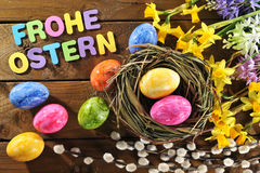 Easter basket. Narcissus, easter eggs and easter basket and Happy Easter lettering on old weathered wooden board Stock Images