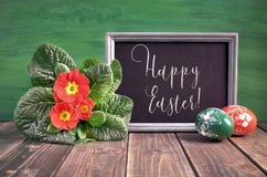 Easter basket with painted Easter eggs and red primrose pot flow Royalty Free Stock Photo
