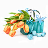 Easter basket with tulips, eggs and wooden butterflies on white Stock Image