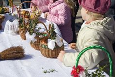 Easter baskets in Poland. A girl standing at a table covered with white tablecloth, Easter eggs are being consecrated Stock Photo