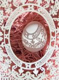 Easter. A beautiful Easter card with an openwork vertical oval frame through which beautiful shadows fall on a white egg. Green royalty free stock images