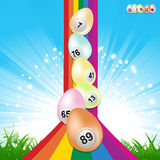 Easter bingo eggs and rainbow. Easter Bingo Eggs Over Rainbow with Star Burst Sky and Grass Background Royalty Free Stock Image