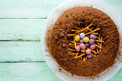 Easter bird nest cake - chocolate cake with pastel candy eggs in Royalty Free Stock Photography