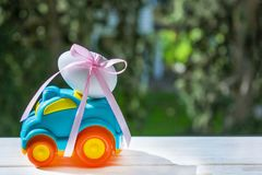 Easter blue cars with a white egg. Easter car of blue color with white egg tied with pink ribbon rides on the table against the background of greenery stock photography