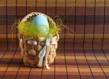 Easter blue egg in a basket of straw stock photos