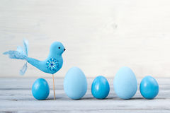 Easter blue eggs and bird on a light wooden background Royalty Free Stock Photos