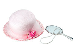 Easter Bonnet and Pearls. Easter bonnet and pearl necklace with silver mirror royalty free stock photography