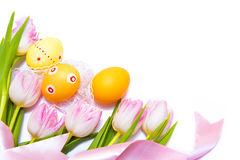 Easter border. Made of painted Easter eggs, pink tulips and silk ribbon on white background stock photography
