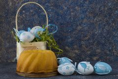 Easter bread and blue Easter eggs in a basket on dark stone table stock image