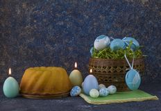 Easter bread and blue Easter eggs in a basket on dark stone table stock photos