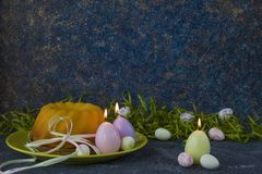Easter bread on green plate and painted Easter eggs ion dark stone table decorated with green grass stock photo