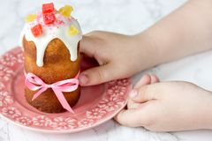 Easter bread kulich paska. On plate in kid hands Royalty Free Stock Image
