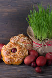 Easter bread with sesame seeds, colored eggs and grass. On wooden table, rustic style, selective focus Stock Photos