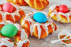 Easter Bread wreaths glazed around dyed eggs. Close-up of homemade sweet Italian Easter Bread Rings glazed around dyed egg and topped with colorful sprinkles on stock photos