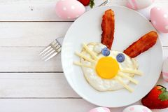 Easter breakfast with bunny face, scene with decor over white wood. Easter breakfast with cute bunny face made of egg and bacon. Flay lay scene with decor over a Royalty Free Stock Photo