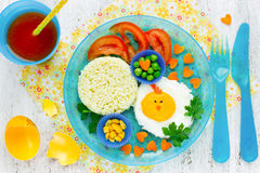 Easter breakfast for the child. Creative idea for baby food. Vegetables and fried egg in the shape of chick. Colorful healthy food concept top view stock images
