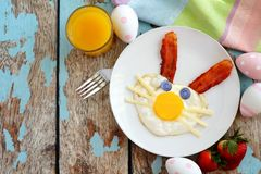 Easter breakfast with cute bunny face, table scene over white wood. Easter breakfast with cute bunny face made of egg and bacon. Table scene, above view over a Royalty Free Stock Photo