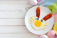 Easter breakfast with bunny face, scene with decor over white wood. Easter breakfast with cute bunny face made of egg and bacon. Top view scene with decor over a Royalty Free Stock Images