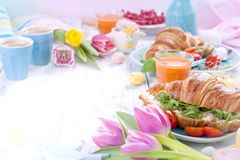 Easter breakfast. A family breakfast of croissants with rocket salad and cheese and aromatic coffee. Fresh tulips of pink color. And eggs of different colors royalty free stock images