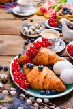 Easter breakfast flat lay with fresh coffee, berries and pastries , orange tulips, croissants with bacon and various sweets ,. Colored quail eggs and spring royalty free stock photography