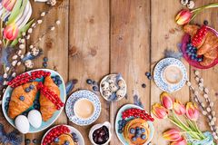 Easter breakfast flat lay with fresh coffee, berries and pastries , orange tulips, croissants with bacon and various sweets ,. Colored quail eggs and spring royalty free stock photos