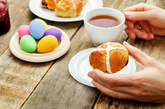 Easter Breakfast. Man holding the bun with a cross and a cup of Royalty Free Stock Photos