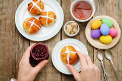 Easter Breakfast. Man holding the bun with a cross and a jar of Stock Images