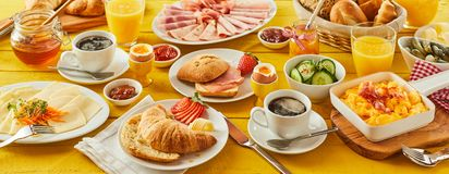 Easter breakfast panorama banner. With a wholesome spread of assorted bread rolls, croissant, cheese, cold meats, orange juice, coffee, honey and preserves Stock Photo