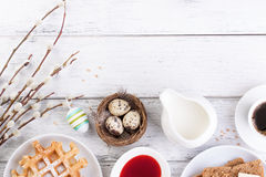 Easter breakfast with quail eggs, waffles, fruit jam, milk, coffee and sandwiches, with willow branch on a white wooden background Royalty Free Stock Photos