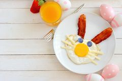 Easter breakfast, table scene with bunny face over white wood. Easter breakfast with cute bunny face made of egg and bacon. Table scene, above view over a white Royalty Free Stock Photo