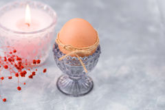 Easter brown egg in a crystal blueish cup, burning pink candle, tender red spring flowers Stock Image