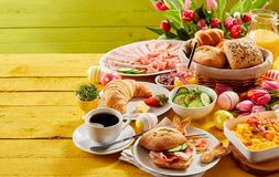 Easter buffet breakfast or brunch. With assorted bread rolls, cheese, meat, scrambled egg, orange juice, coffee on a wooden table decorated with easter eggs and royalty free stock images