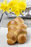 Easter bun and bouquet of daffodils Stock Image