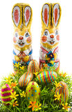 Easter bunnie. Two chocolate bunnies with chocolate eggs in the grass on a white background Royalty Free Stock Photos