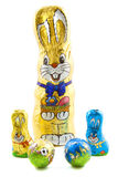 Easter bunnie. Four chocolate bunnies in foil with two chocolate balls isolated over white Stock Photography