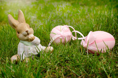 Easter bunnie and blue Scilla. Easter bunnie and pink eggs are outdoors Stock Photos