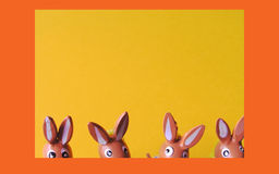 Easter bunnies 2. Four toy bunnies, on yellow background with orange frame Royalty Free Stock Images