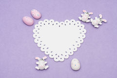 Easter Bunnies. And eggs sitting with a white  heart on purple background Royalty Free Stock Photo