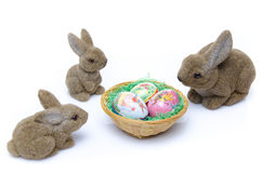Easter bunnies around a nest of eggs Royalty Free Stock Photo