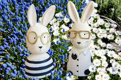 Happy easter- Easter bunnies in blue grape hyacinths, white anemones Royalty Free Stock Photo