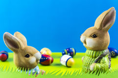 Easter bunnies on blue background. Easter bunnies and colored eggs on blue background Royalty Free Stock Image