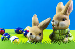 Easter bunnies on blue background. Easter bunnies and colored eggs on blue background Royalty Free Stock Photography